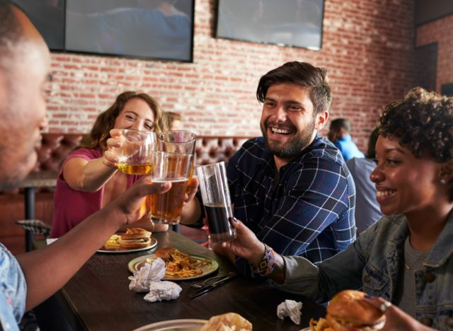 Friends Eating Out In Sports Bar With Screens In Background