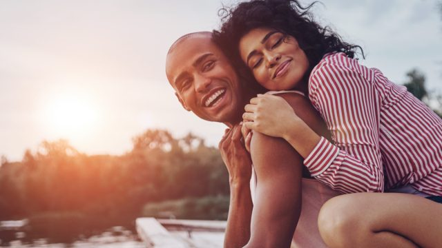 Happy young couple embracing and smiling while sitting on the pier near the lake