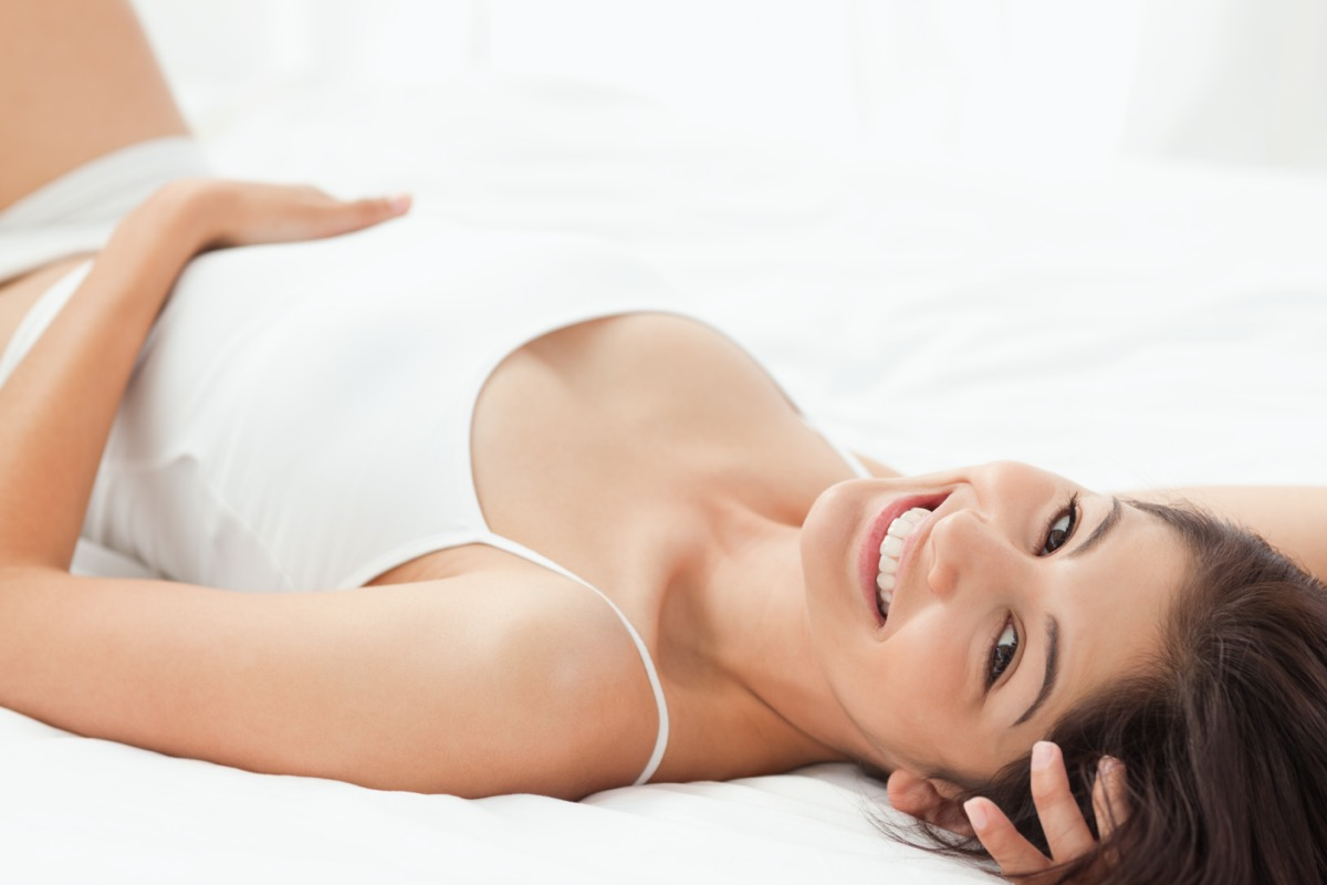 A woman smiling as she lies on her back with on hand on her stomach and the other under her head.