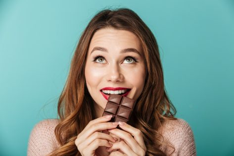 Portrait of a delighted brown haired woman with bright makeup eating chocolate bar