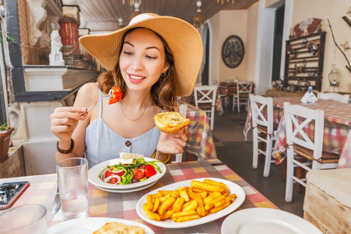 Happy asian woman in big hat having meal with greek salad Horiatiki in restaurant. Greece cuisine concept