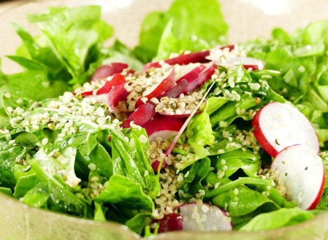 Hemp seeds on green leaf salad