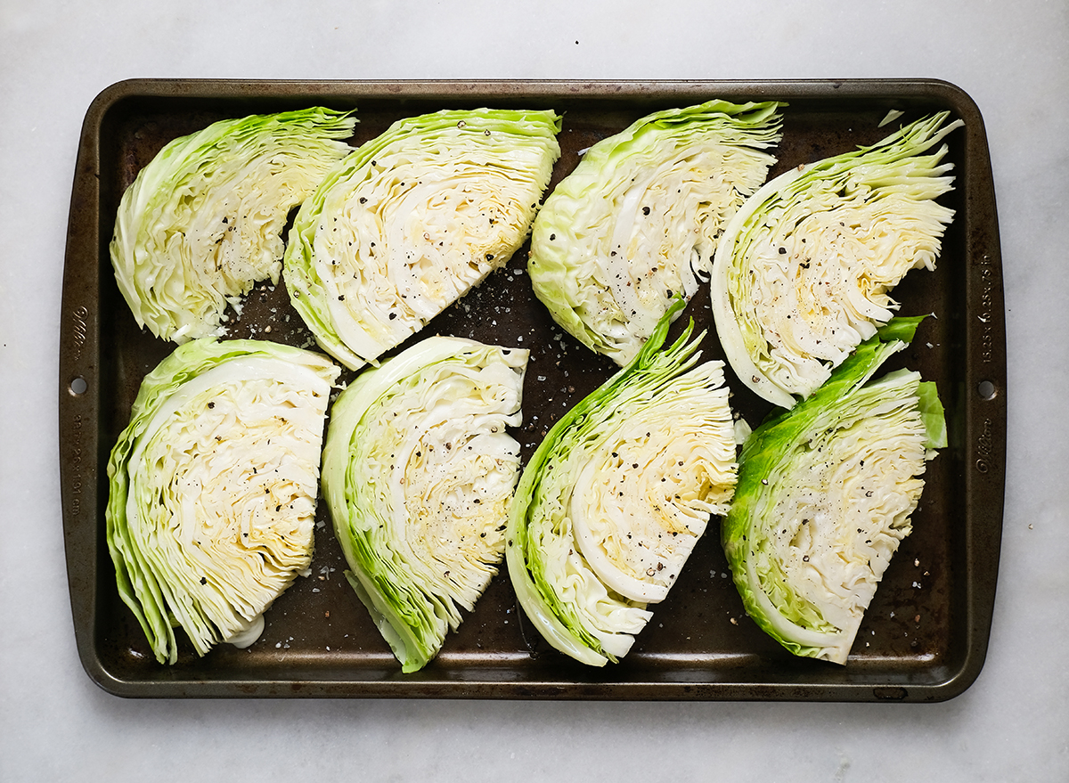 cabbage wedges seasoned with salt and pepper on a baking sheet
