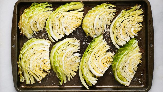 cooked cabbage wedges on a baking sheet