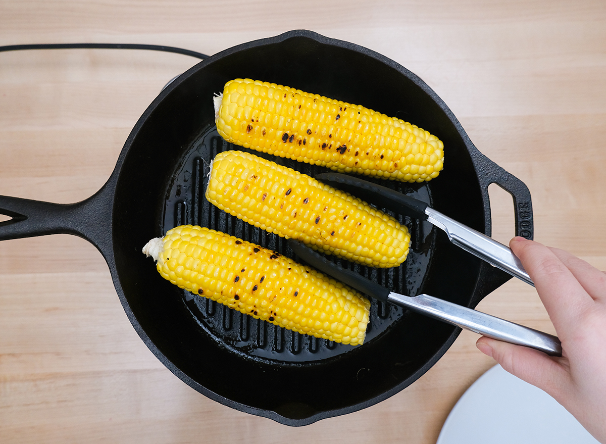 cooking corn on a cast iron grill with oil