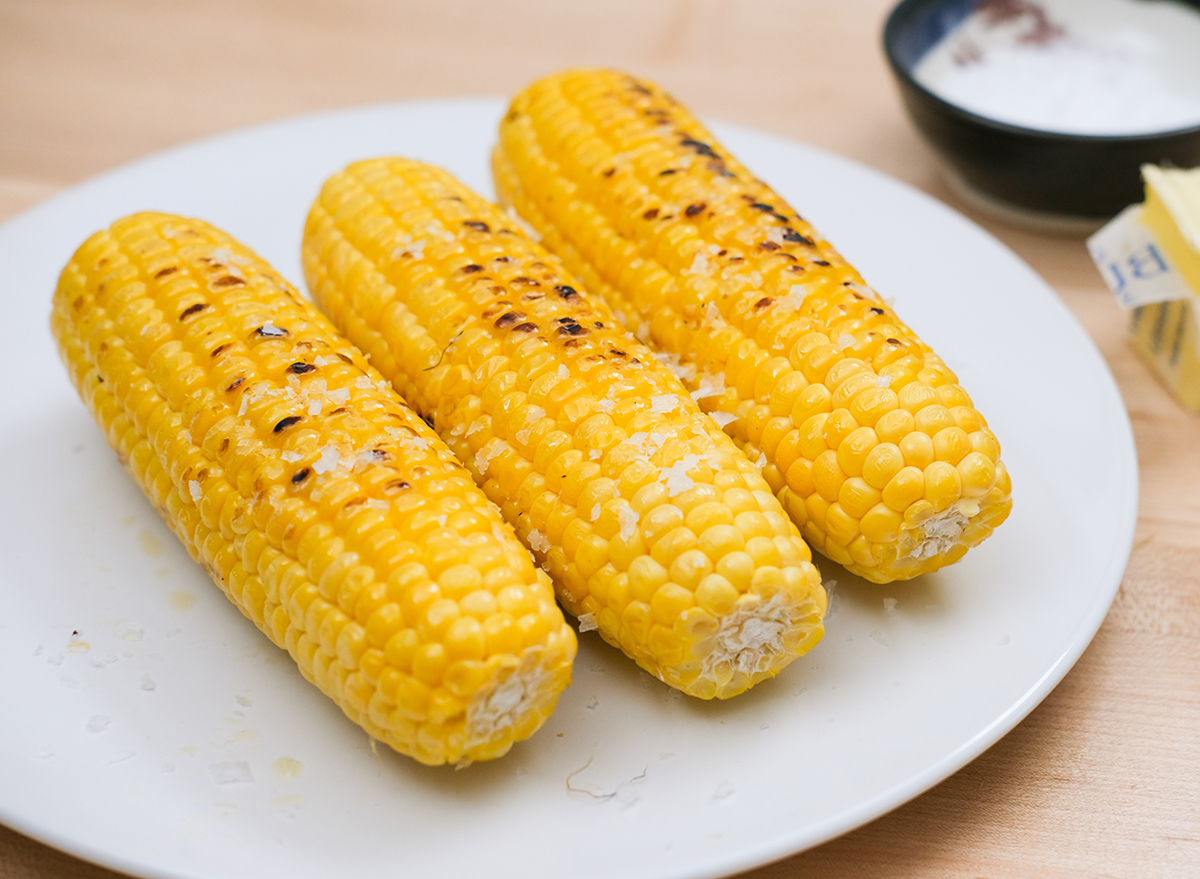 cooked corn on the cob with butter and salt on a plate