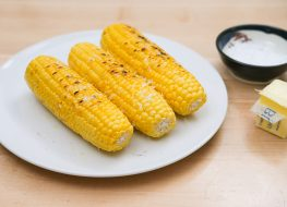 cooked corn with salt and butter on a plate