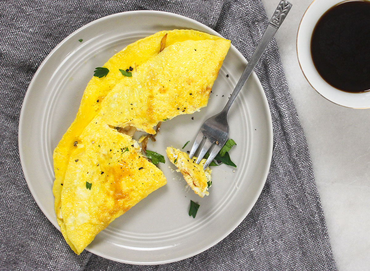 breaking into a cooked omelet on a grey plate