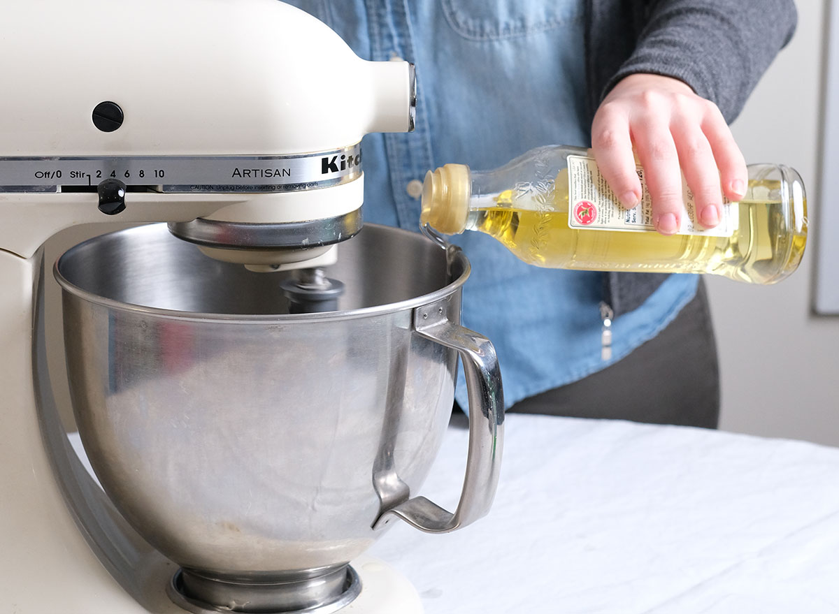 slowly pouring oil into a stand mixer