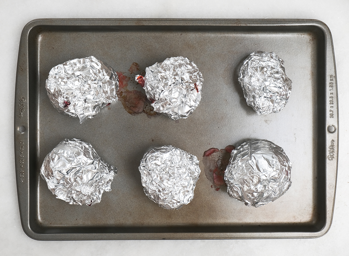 roasted beets wrapped in aluminum foil on a baking sheet