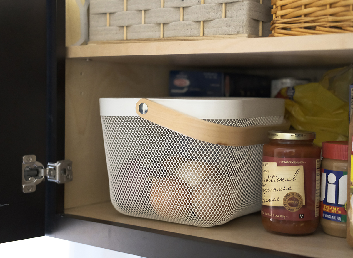 onions in a basket stored in a cabinet