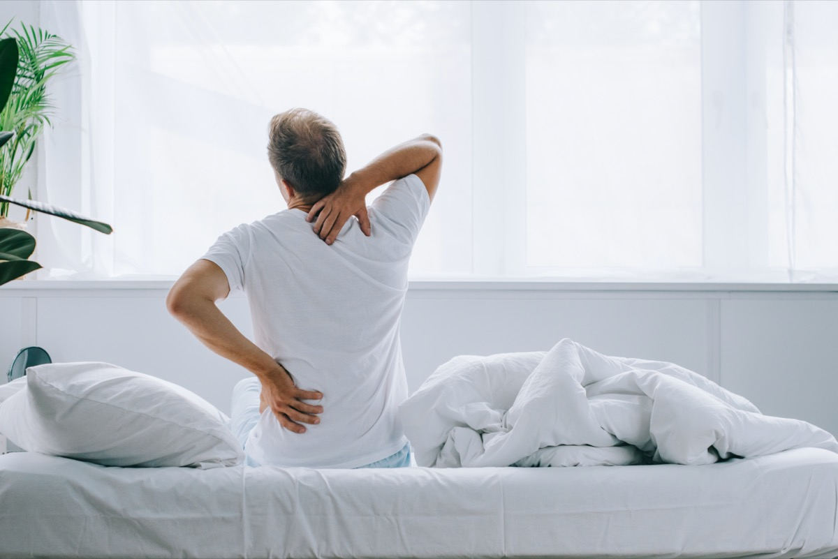 back view of man sitting on bed and suffering from back pain