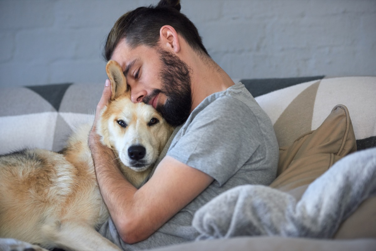 man snuggling and hugging his dog, close friendship loving bond between owner and pet husky