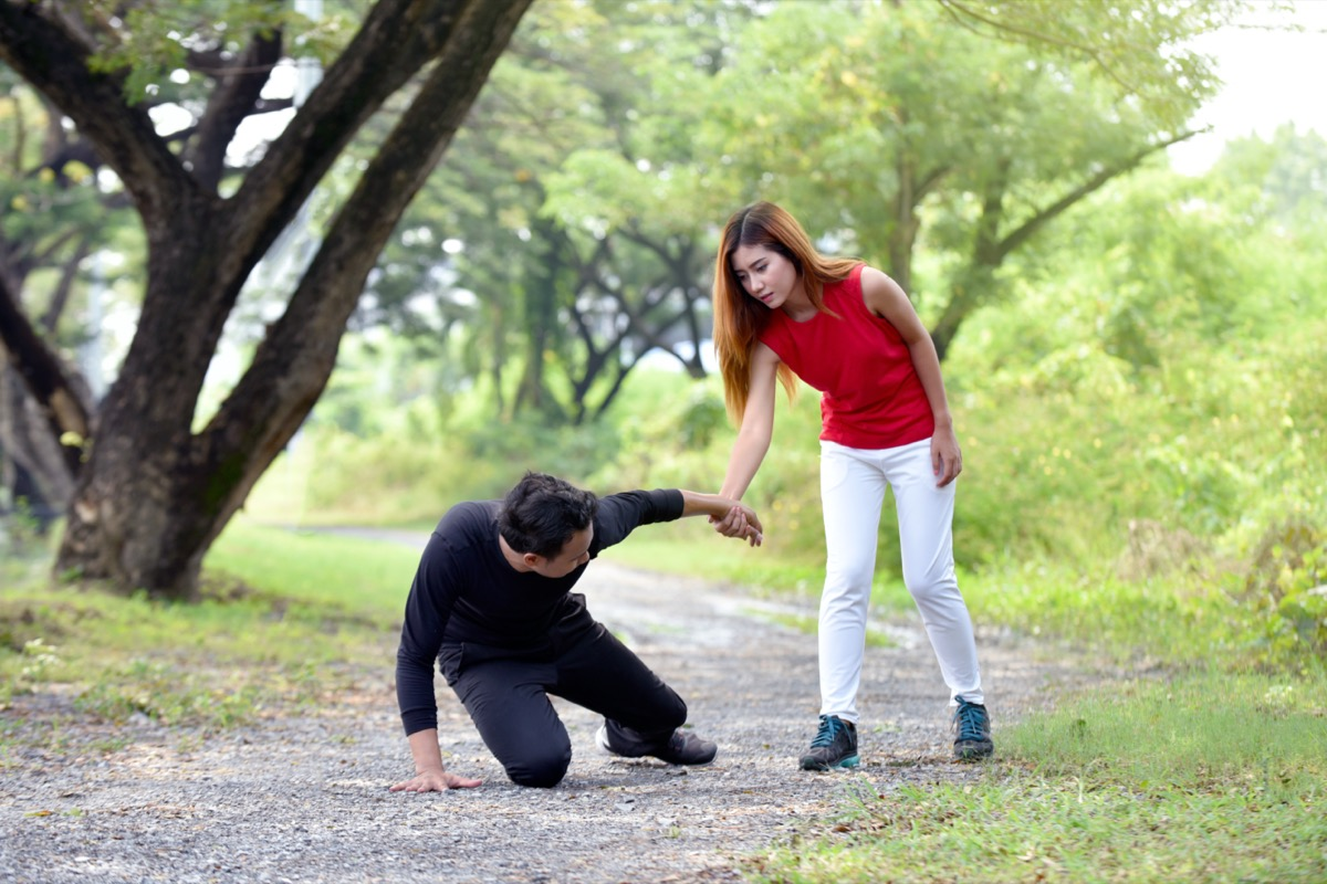 Woman assisting an injured man on the running track at garden