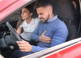 Young woman and man suffering from heart attack in car