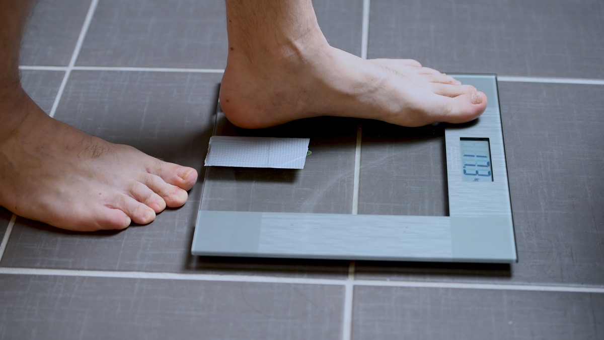 Male feet on glass scales, men's diet, body weight, close up, man stepping up on scales