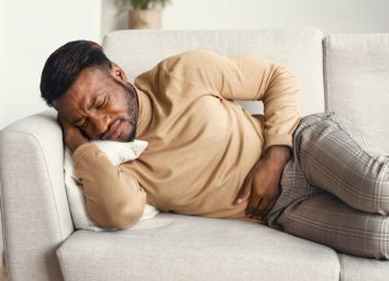 Suffering From Abdominal Pain Touching Aching Stomach Lying On Couch At Home