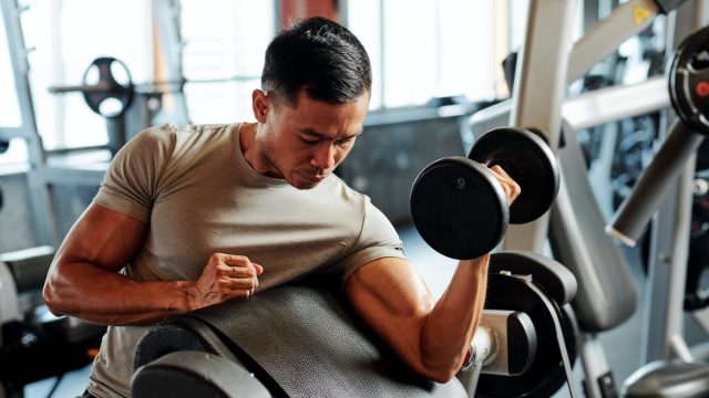 Fit serious Asian sportsman exercising with weights in gym