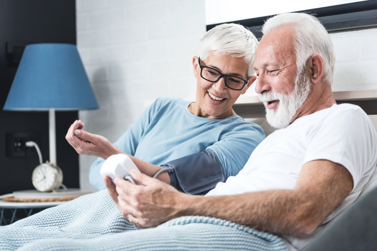 Senior couple in pajamas in a bed in a bedroom measure each other's blood pressure. Concept of home health check