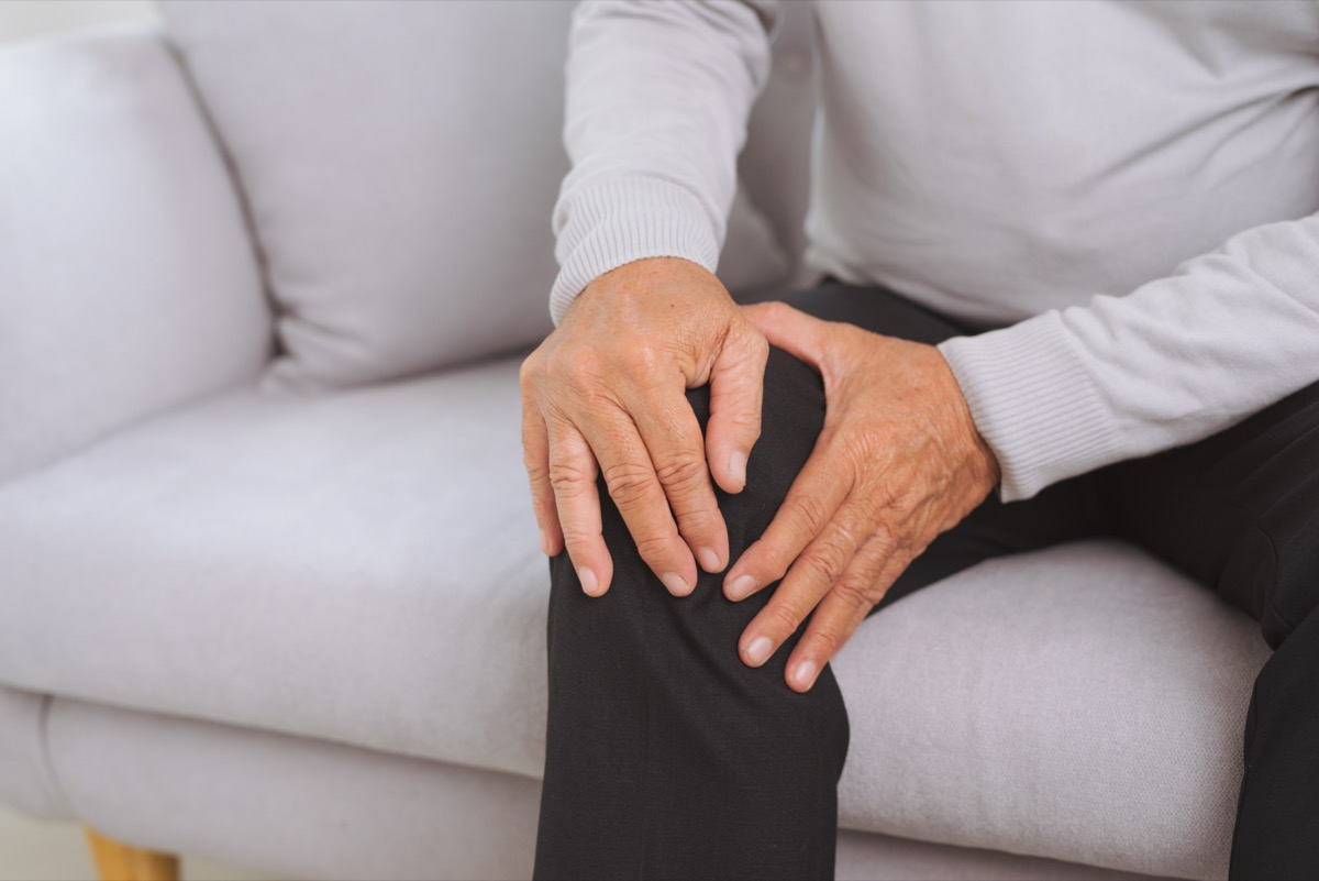 Senior man sitting on a sofa in the living room at home and touching his knee by the pain.
