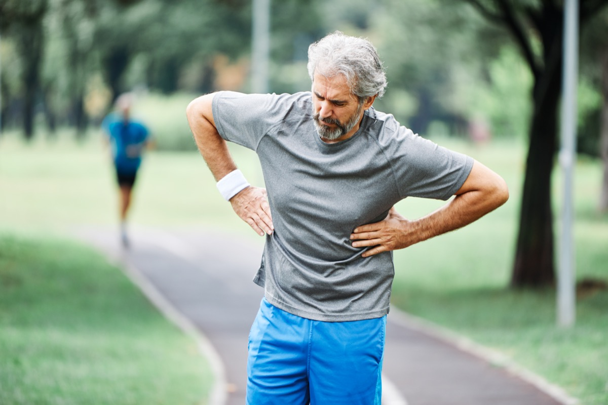 portrait of a senior man exercising and running outdoors having cardio problems chest pain