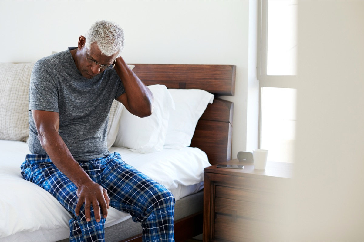 Senior Man Suffering With Neck Pain Sitting On Side Of Bed At Home