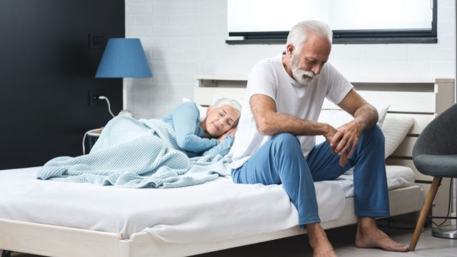 Worried senior depressed man sitting in bed and suffering from insomnia while his wife sleep