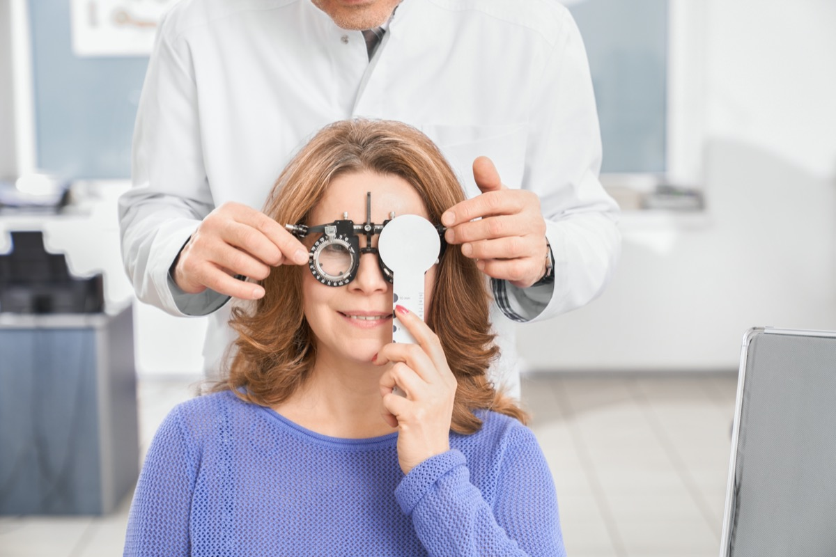 Doctor ophthalmologist examining eyesight of patient with special medical device