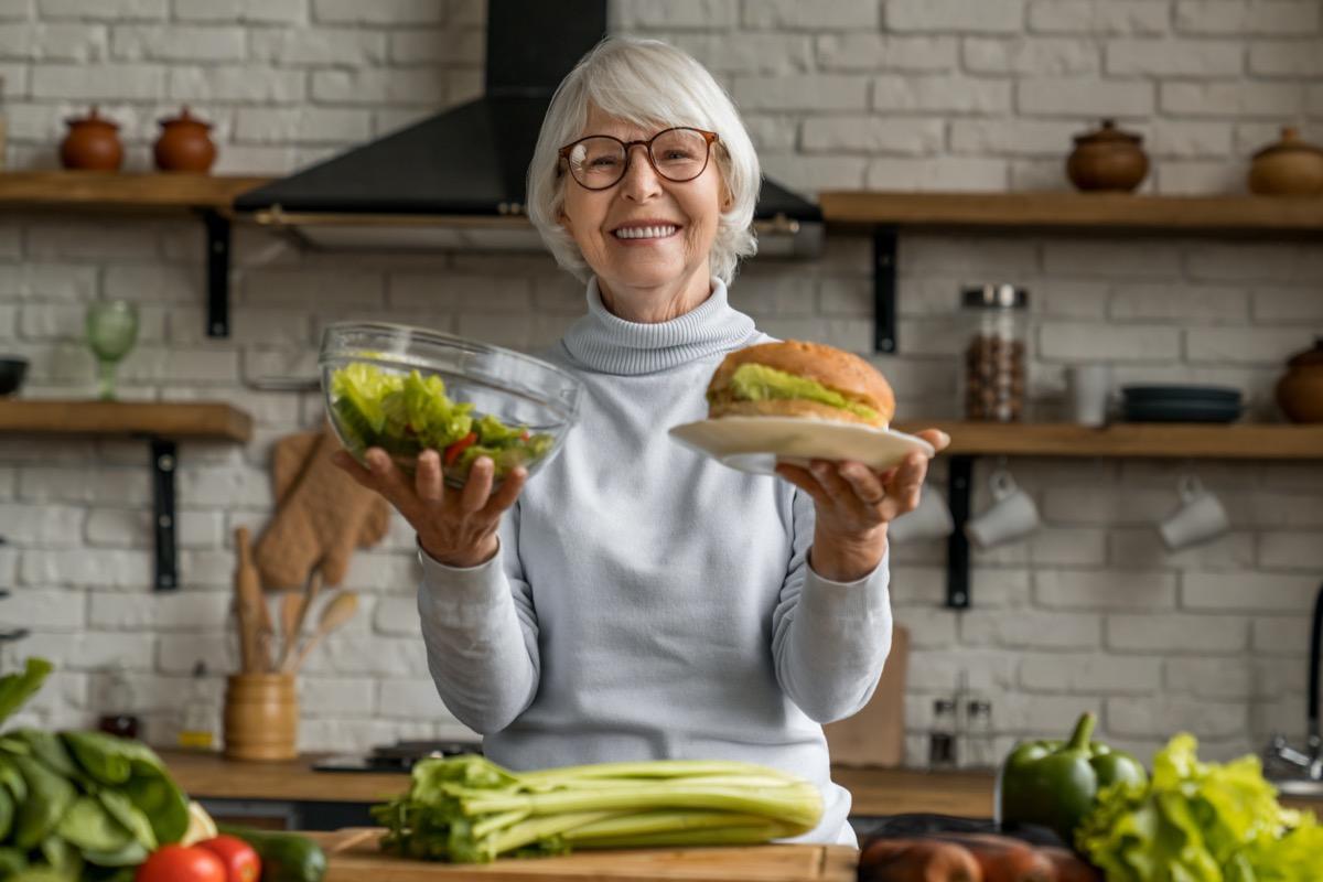 Senior woman making choice between healthy and junk food