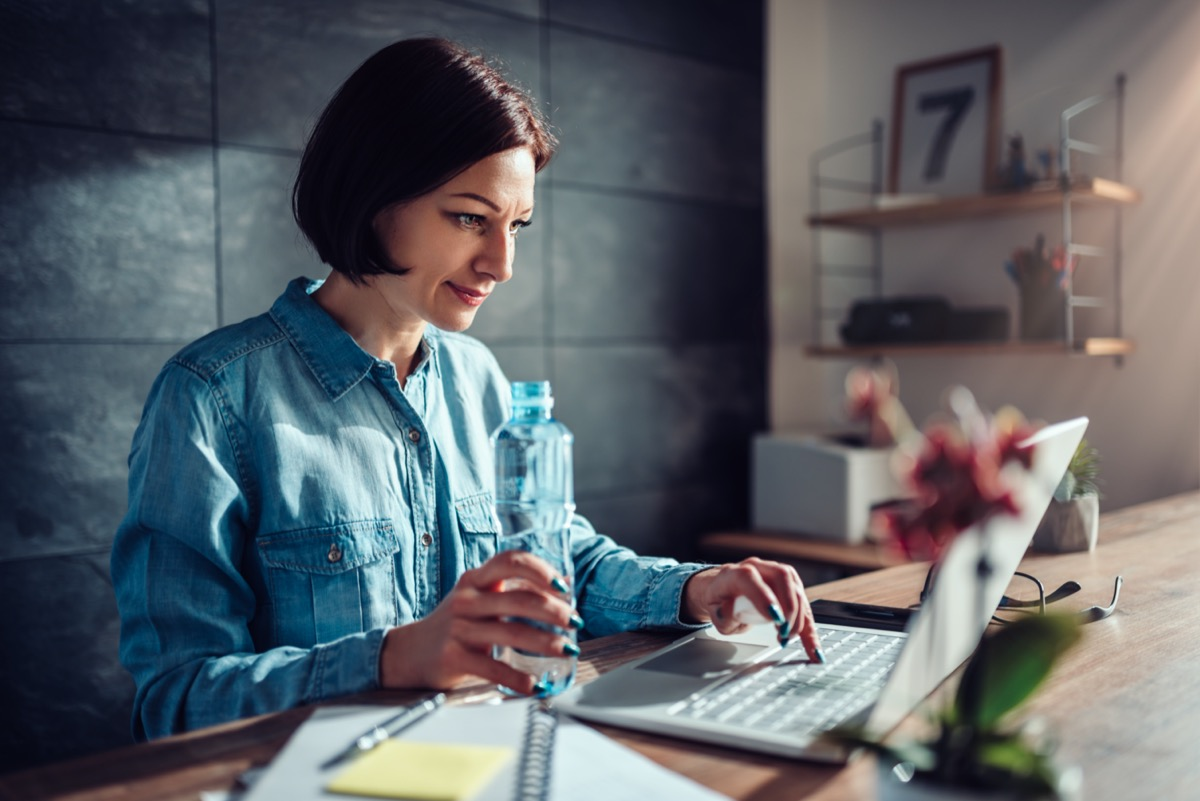 Woman wearing denim shirt using laptop in the office and holding plastic bottle of water