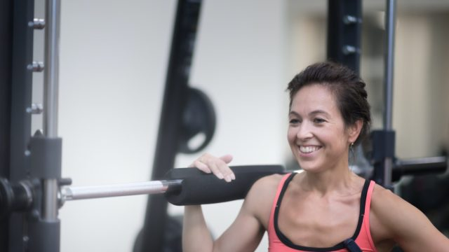middle age woman in red shirt is standing in the gym near the rod