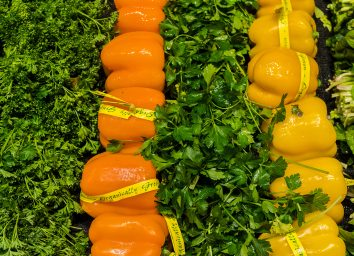 organic orange and yellow bell peppers in grocery store