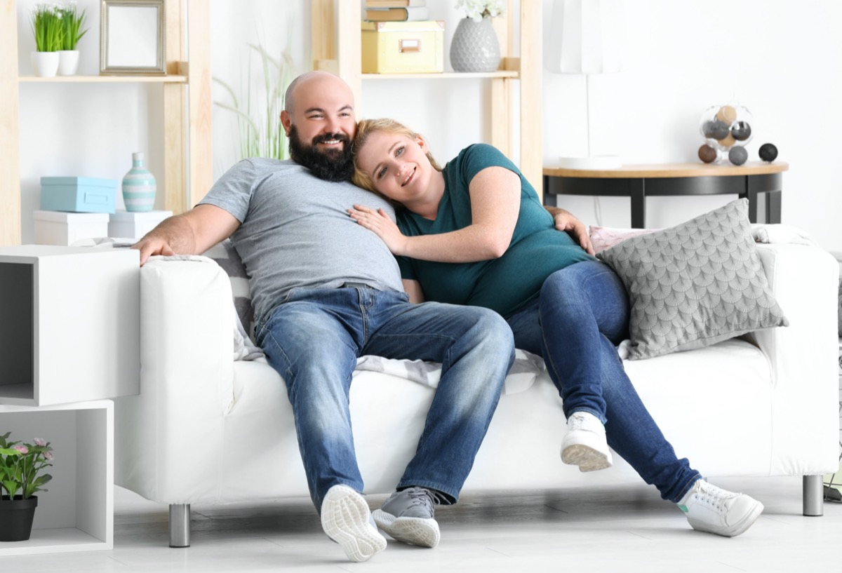 Overweight couple watching tv at home