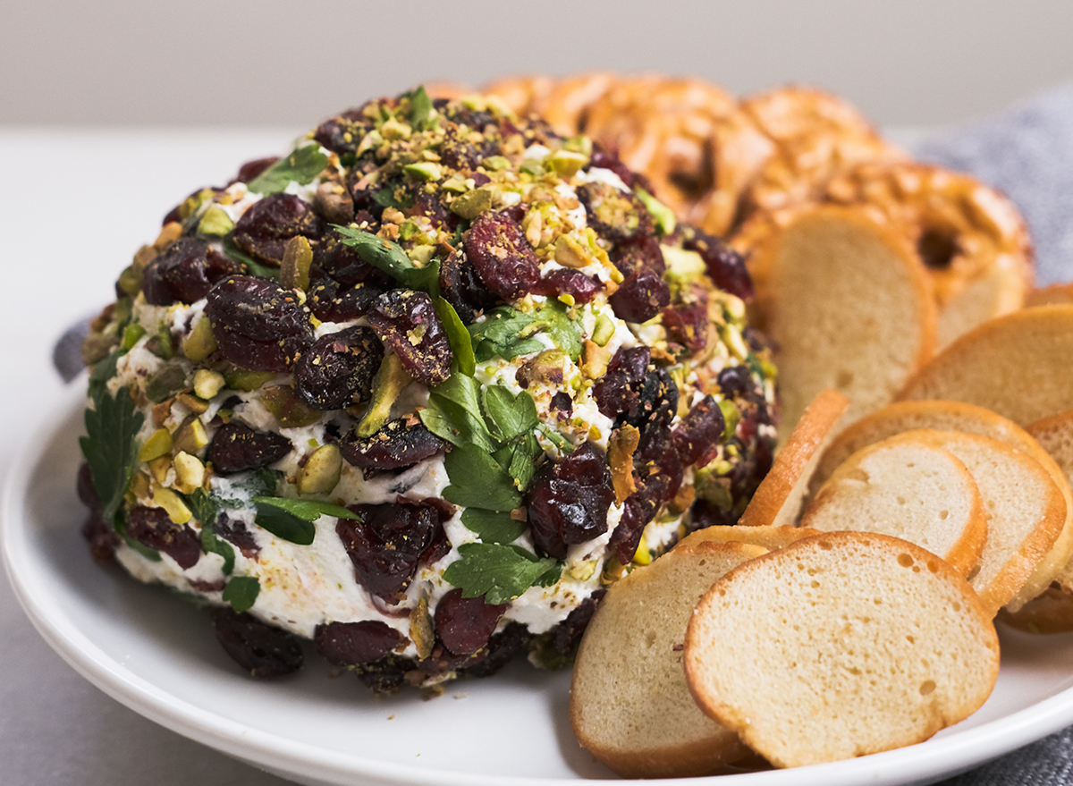 pistachio cranberry cheese ball with snacks on a plate