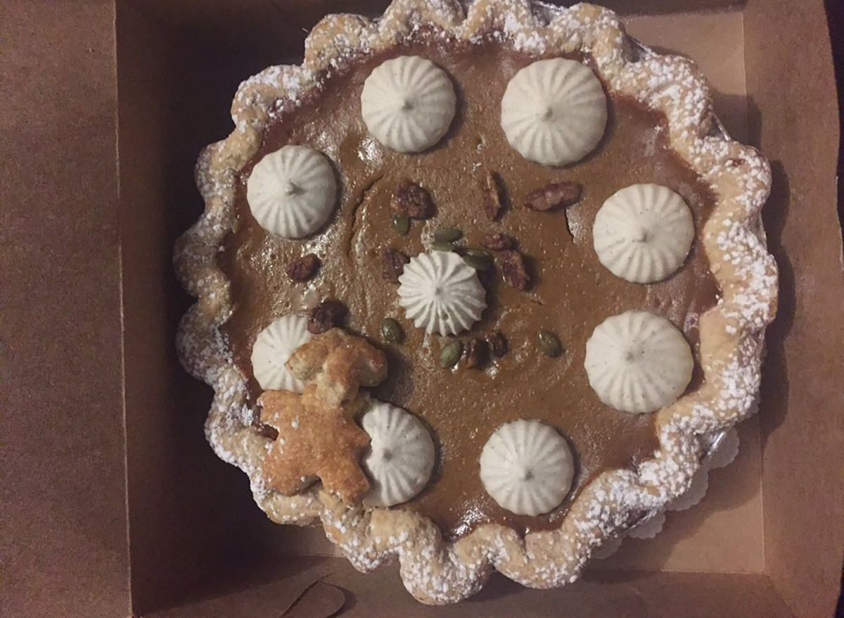 whole pumpkin pecan pie with whipped cream and pumpkin seeds