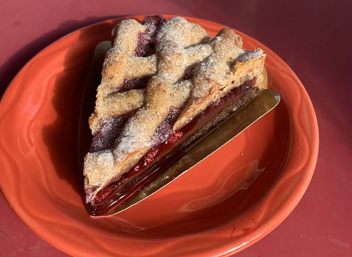 slice of raspberry pie on red plate