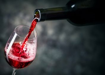 red wine being poured from bottle into glass