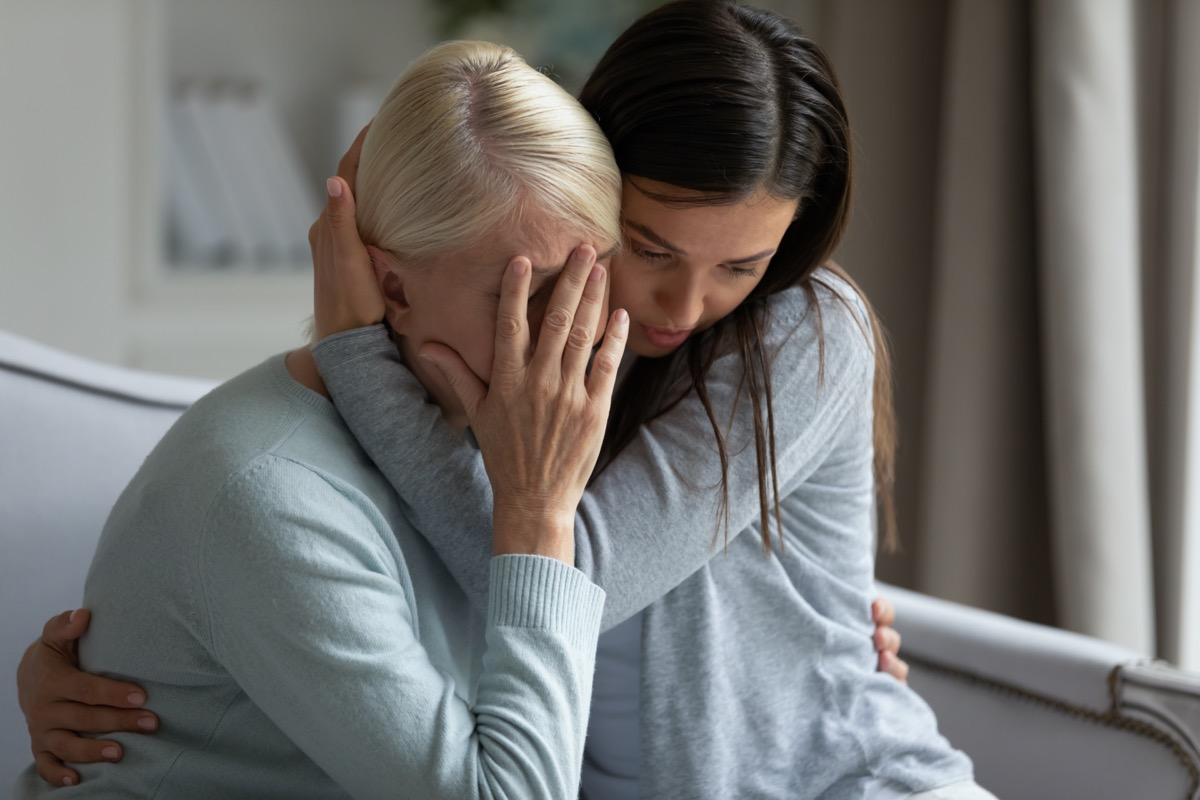 Empathic young lady embracing soothing crying depressed elder mommy, sitting together at home
