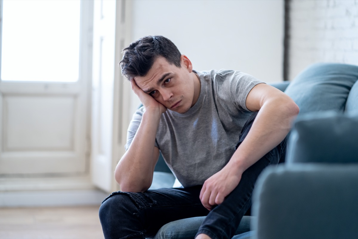 Portrait of young man felling depressed and desperate crying alone in sofa home suffering emotional pain and unhappiness