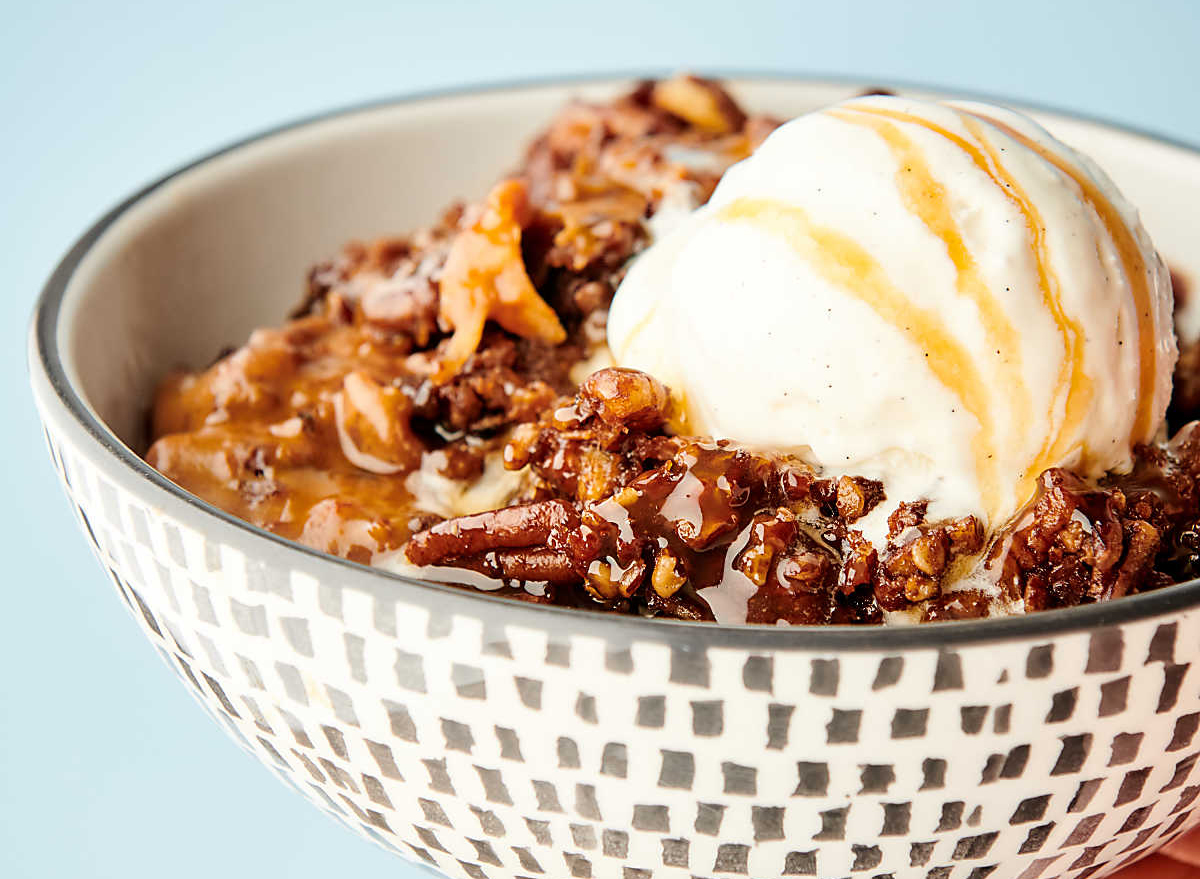slow cooker carrot cake topped with vanilla ice cream in bowl