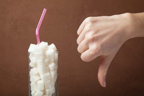 Sugar cubes in glass and hand shows thumbs down.