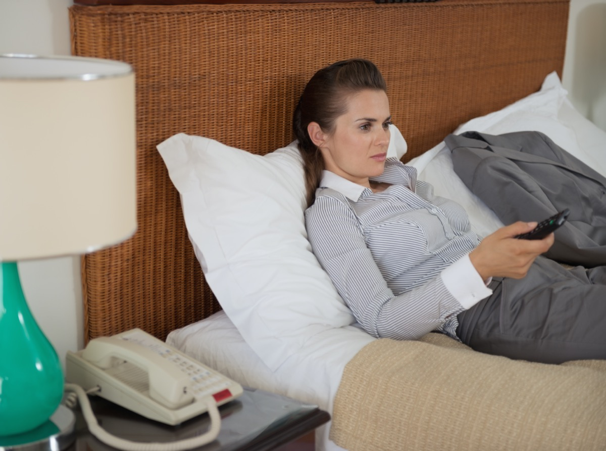 Tired business woman watching tv in hotel room