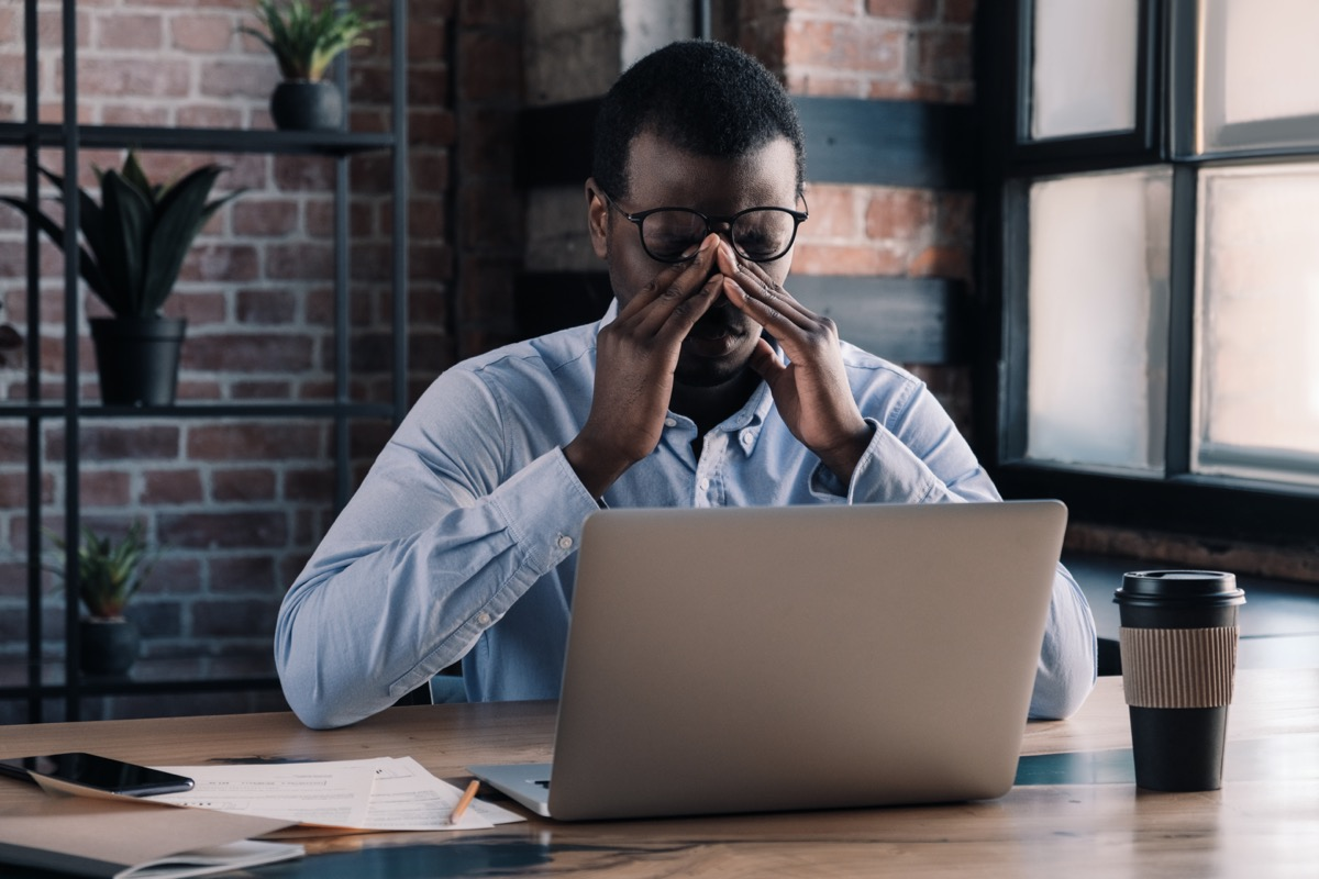 Tired african business man massaging his nose with eyes closed, sitting at his desk in office