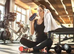 Young woman drinking water and taking a break after workout in gym,