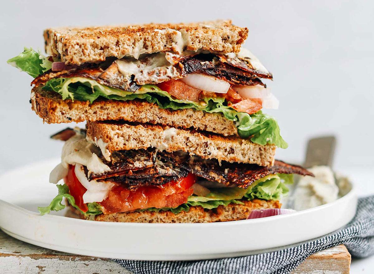 vegan blt sandwich halves stacked on serving platter
