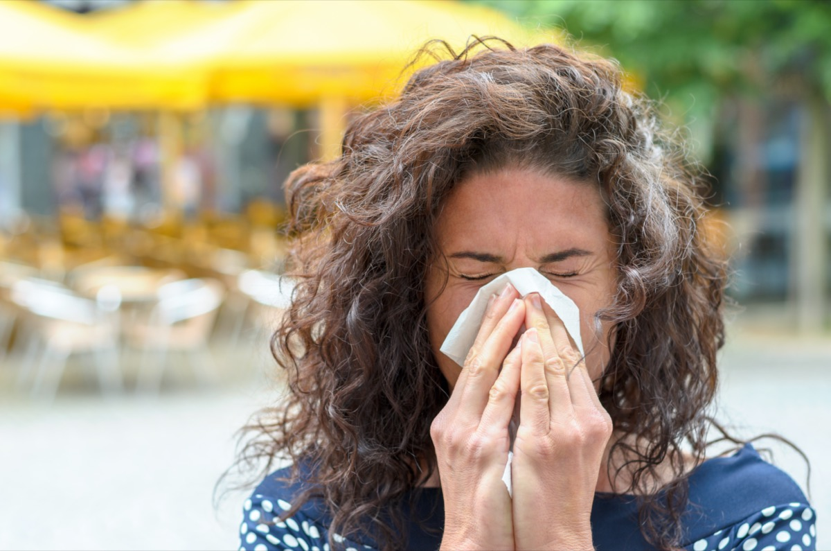 woman with lovely long curly hair standing outdoors blowing her nose in an urban square due to a seasonal cold or hay fever