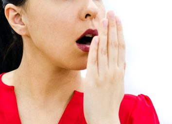 Woman checking her breath with hand