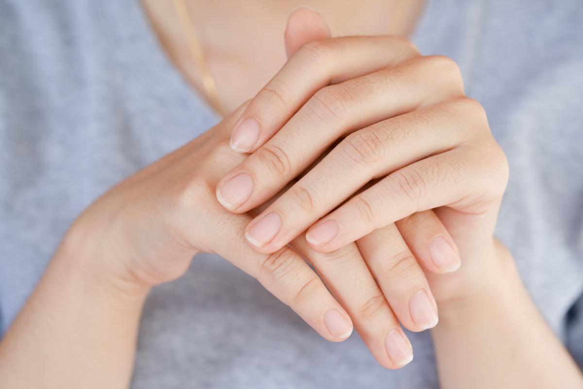 Woman looking at fingernails