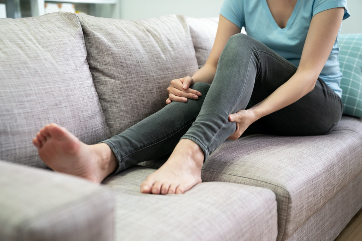 unrecognized young asian woman had pain at calves sitting on couch at home