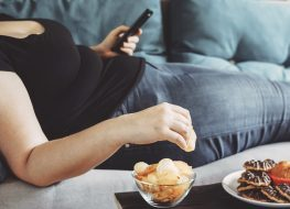 Woman emotional eating chips on couch scrolling through phone